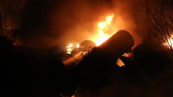 Derailed oil tanker train cars burn near Mount Carbon, W.Va., Monday, Feb. 16, 2015. A CSX train carrying more than 100 tankers of crude oil derailed in a snowstorm, sending a fireball into the sky and threatening the water supply of nearby residents, authorities and residents said Tuesday. (AP Photo/The Daily Mail, Marcus Constantino)