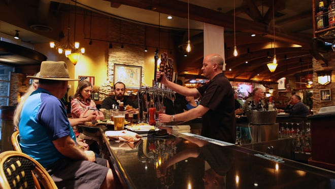 Jason St.John, the manager at Babe's Bar-B-Que & Brewhouse at The River in Rancho Mirage, pours beer for a patron.  Photographed on Monday, February 23, 2015.
