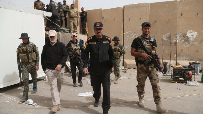 Lt. Gen. Abdul-Wahab al-Saadi, center, Iraqi forces commander in Tikrit, inspects his forces at the front line in Tikrit, 130 kilometers (80 miles) north of Baghdad, Iraq, Friday, March 13, 2015. Iraqi forces entered Tikrit for the first time on Wednesday from the north and south. On Friday, they fought fierce battles to secure the northern Tikrit neighborhood of Qadisiyya and lobbed mortars and rockets into the city center, still in the hands of IS. Iraqi military officials have said they expect to reach the center of Tikrit within two to three days. (AP Photo/Khalid Mohammed)
