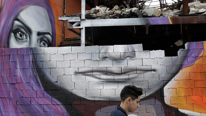 A man walks past graffiti by Greek street artist Achilles in Athens on April 8, 2015.