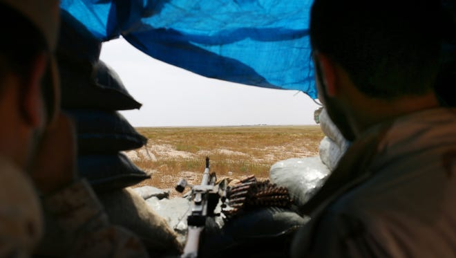 In this Monday, April 20, 2015 photo, two Sunni fighters overlook an Islamic State group-held village on the other side of the frontline in northern Iraq. The Sunni men face their own tribesmen who are fighting alongside the Islamic State group. (AP Photo/Bram Janssen)