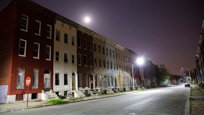 The moon rises above a block of blighted row houses in the neighborhood where Freddie Gray was arrested as a six day curfew was lifted Sunday in Baltimore.