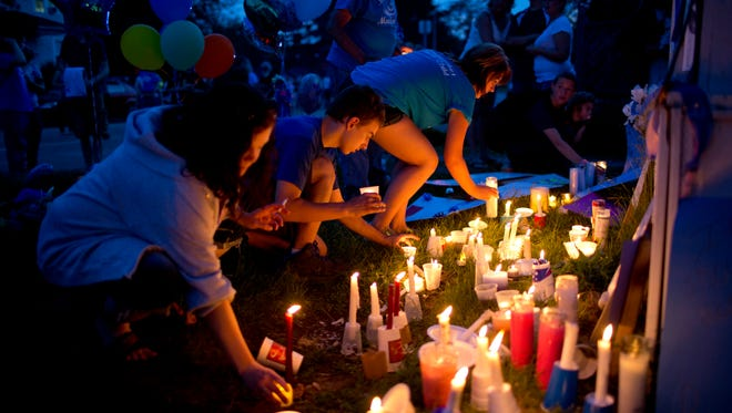 People place candles at a vigil in memory of 5-year-old Mackenzie Maison Friday, May 29, 2015 in the 800 block of Oak Street in Port Huron.