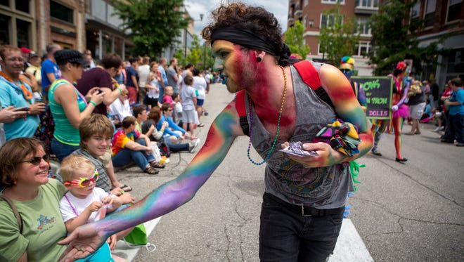 A participant hands out cards in the 2013 Pridefest parade.