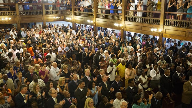 Parishioners applaud during a memorial service at Morris Brown AME Church for the people killed Wednesday during a prayer meeting inside a historic black church in Charleston, S.C., Thursday. Police arrested 21-year-old suspect Dylann Storm Roof Thursday in Shelby, N.C. without resistance.