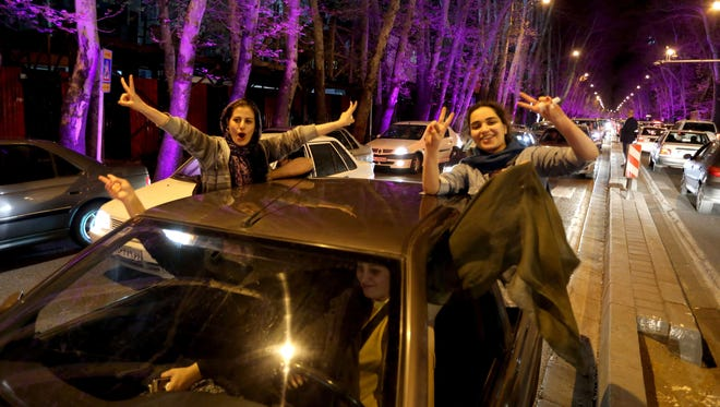 """Women sitting in a car flash the """"V for Victory"""" sign as they celebrate in northern Tehran in April after the announcement of an agreement on Iran nuclear talks. Iran and global powers sealed a deal April 2 to curb Tehran's chances for getting a nuclear bomb, laying the ground for a new relationship between the Islamic republic and the West."""