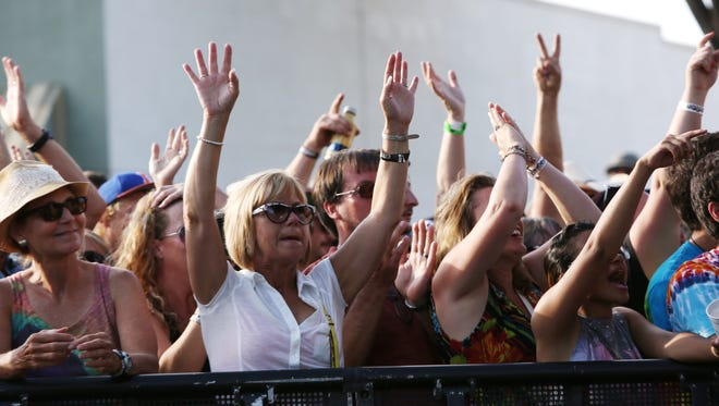 Fans raise their arms as War performs during the last day of Bohemian Nights NewWestFest Aug.17, 2014.