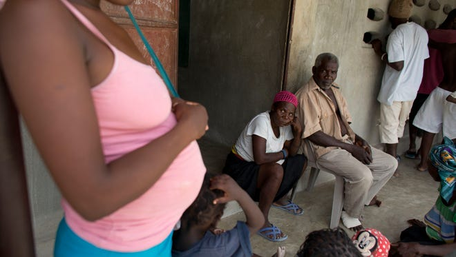 Haitians recently deported from neighboring Dominican Republic sit outside a school building where residents have allowed them to stay in the village of Fond Bayard, Haiti.