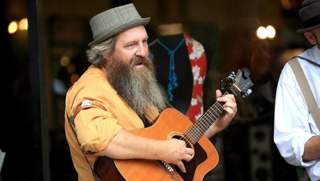 A busker performs in downtown Asheville.