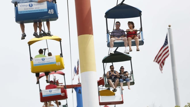 Tom and Colleen Sharer (top right) of Gilbert, Ariz., ride the Sky Glider over the fairgrounds Thursday, Aug. 13, 2015, during opening day at the Iowa State Fair in Des Moines. The couple used to live in Marshalltown, and are in Iowa visiting family.