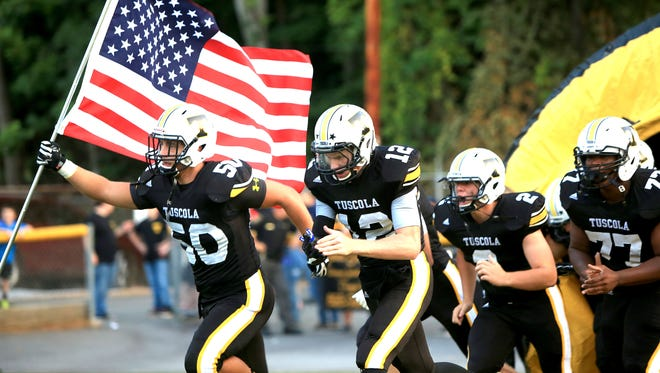 Tuscola football players take the field last Friday in Waynesville.