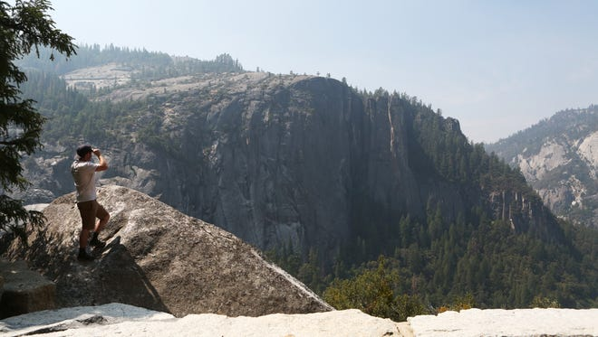 A park visitor looks out at the view at a turnout on Big Oak Flat Road overlooking Yosemite Valley on Sunday, August 23, 2015 in Yosemite National Park, Calif.