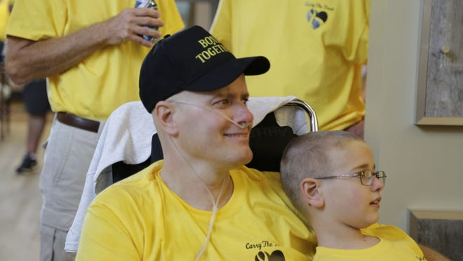 Scott Bond smiles Sunday, Sept. 27, 2015 while holding his son, Luke, 8, and listening to his daughter, Kristin, 11, sing a song to him at The Springs at Lafayette. Bond has a terminal form of cancer.
