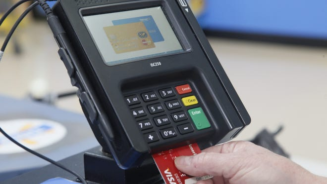 Photo illustration. Reporter Patt Johnson demonstrates how to use a bank card with chip technology at Walmart in Ankeny, Iowa, Tuesday, Sept. 29, 2015.
