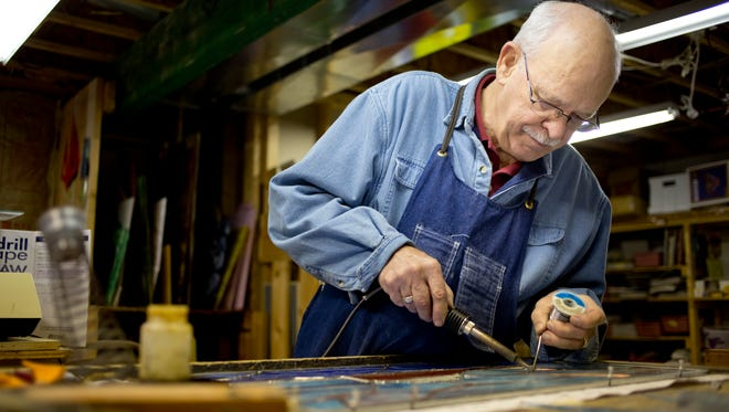 Rick Cameron works on a commissioned stained-glass piece Wednesday in his workshop at his home in Clyde Township.