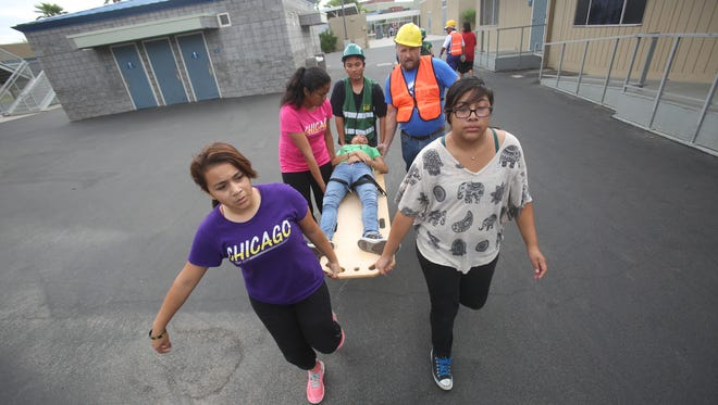 Cathedral City High School students and staff participate in the Great Shake Out, which is an international earthquake drill that happens on October 15. Cathedral City High School also gave experience to their health academy students. In this photo a student playing an injured girl is transported to safety.