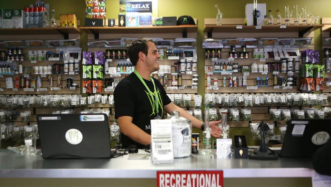 Ian Azzam, a bud tender at the Medicine Man dispensary and grow facility in Denver, works behind the counter on Monday afternoon.