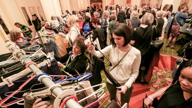 Swapper Stephanie Kinney, center, raids the racks during Style Swap Indy, held at the Omni Severin Hotel, Oct. 22, 2015.