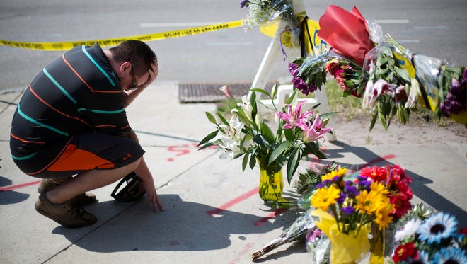 Noah Nicolaisen of Charleston, S.C. kneels June 18, 2015, at a makeshift memorial near where a man opened fire during a prayer meeting inside the Emanuel AME Church, killing several people in what authorities called a hate crime.