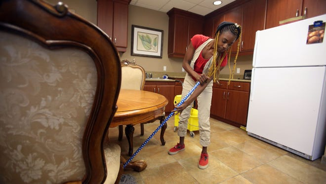 Jennifer Harvey, 23, cleans a dining area at Safe House of the Desert on Thursday October 8, 2015 in Thousand Palms.