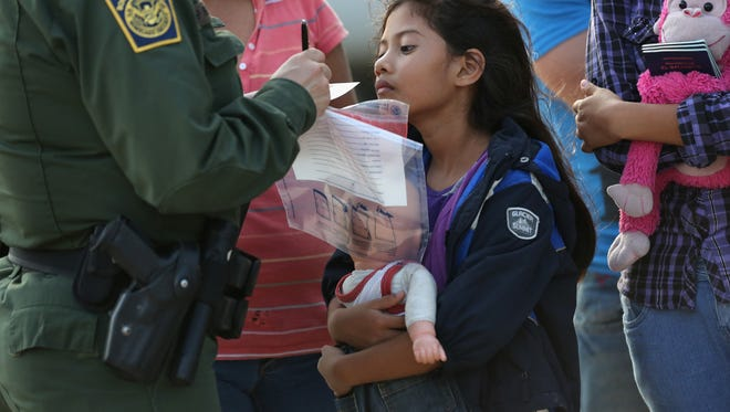 Salvadoran immigrant Stefany Marjorie, 8, watches as a U.S. Border Patrol agent records her information July 24, 2014, in Mission, Texas. She was one of the tens of thousands of children from Central America who fled to the USA that year.