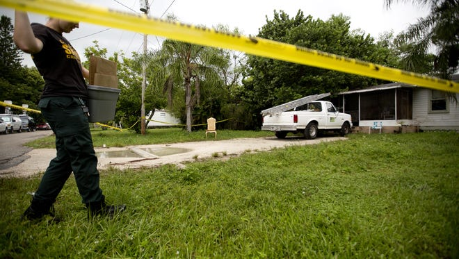 Lee County Sheriff's Office crime scene technician Lindsay Thomson gathers evidence Monday at 238 Capitol St., in North Fort Myers, where the body of Tamara Jean Davis was found. Her son, Tyrese Landrum, 15, was charged in the slaying Sunday after neighbors reported a strong odor coming from the home.
