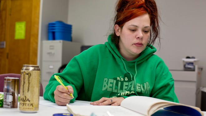 "Tabatha Taylor, of Port Huron, works on grammar exercises in a textbook Wednesday, November 4, 2015 in the Literacy and Beyond G.E.D. Prep Lab at First Congregational Church in Port Huron. Taylor, a recovering drug addict, is working toward getting a college education. ""I want to pass with honors,"" Taylor said."