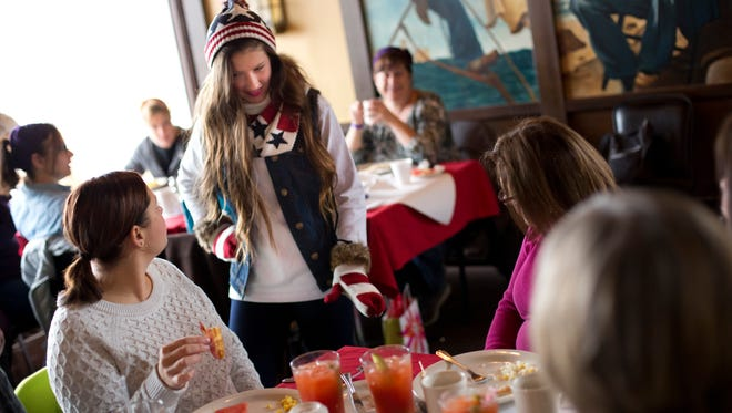 Cortney Nantroup, 15, of Burtchville Township, shows off winter wear from a local store during breakfast and a fashion show as part of the Girlfriend's Getaway Weekend Saturday, November 14, 2015 at The Windjammer in Lexington.