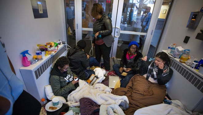 Members of Black Lives Matter and the community sit in the lobby of the Minneapolis Police Department's fourth precinct headquarters in north Minneapolis, Monday, Nov.16, 2015, in the wake of a police shooting that critically wounded a man over the weekend, in Minneapolis.