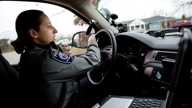 Marine City Police Officer Margie Springer uses her radio to call in a traffic stop to dispatch while on patrol Wednesday, November 18, 2015 in Marine City.