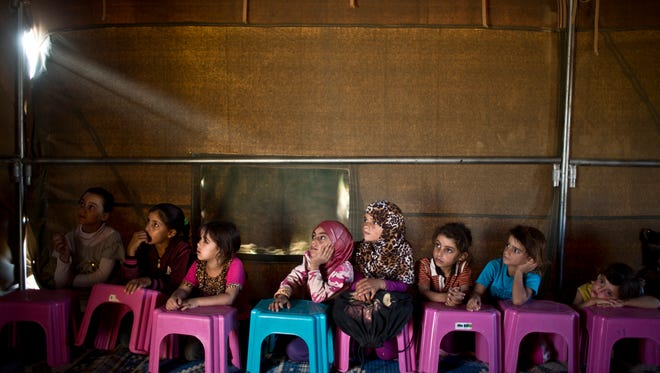 Syrian refugee children attend a class at a makeshift school set up in a tent at an informal tented settlement near the Syrian border on the outskirts of Mafraq, Jordan.