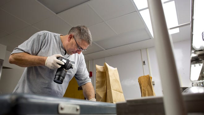 Forensic Investigator Bob Wiley photographs human bones that were found in Burtchville Township Friday, November 20, 2015 in the morgue at McLaren Port Huron.