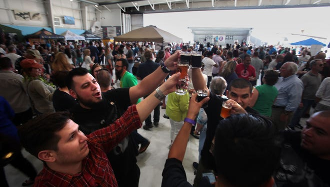 A group of Coachella Valley friend toast each other during the 4th annual Props and Hops festival at the Palm Springs Air Museum on Saturday.