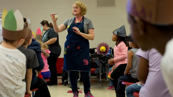 Kindergarten teacher Andrea Cansfield tells students how to make their own butter during a party before the beginning of Thanksgiving break Friday, November 20, 2015 at Cleveland Elementary School.