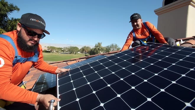 Renova Solar workers Victor Alomar, of Desert Hot Springs, and Eric Quintero, of Coachella, install solar panels on a home in the Mission Hills Country Club in Rancho Mirage on Nov. 25, 2015.