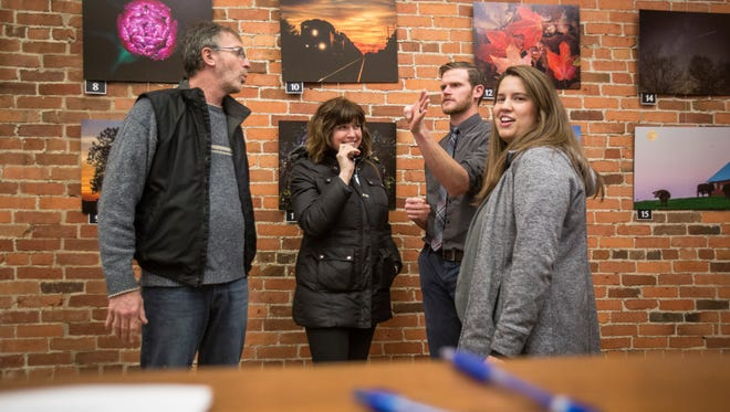Jordan Kartholl talks with several people at The Star Press Holiday Fund photo exhibit Thursday night in downtown Muncie.