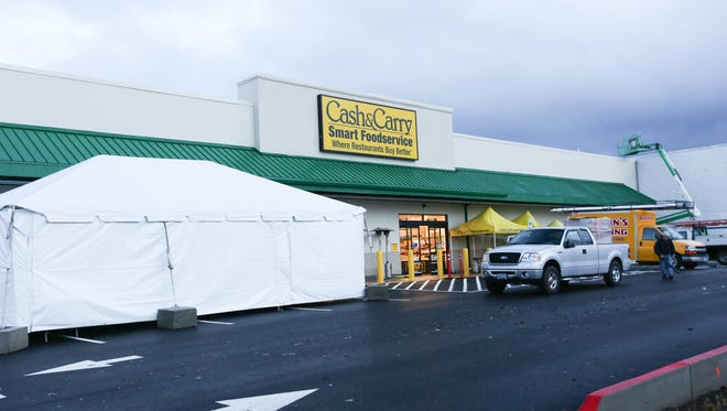 Workers put the finishing touches on the new Cash & Carry store in South Salem on Monday, Dec. 7, 2015.