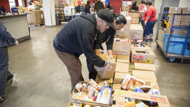 Ernesto Garcia (in front) packs food boxes at St. Mary's UOP Programs Center.