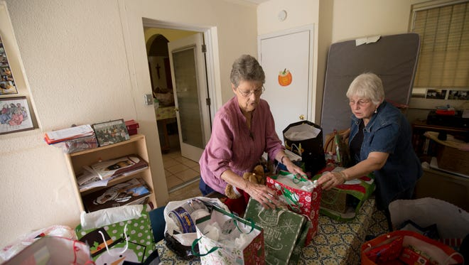 Good Shepherd Ministries of Southwest Florida co-pastors Rev. Judy Lee, right, and  Rev. Judy Beaumont sort gifts at their church off of Central Avenue in Fort Myers.
