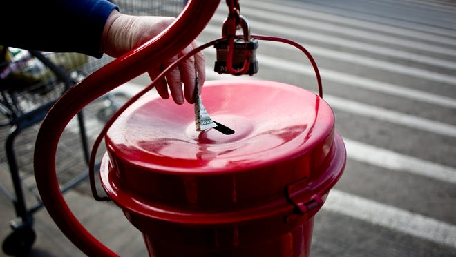 A woman gives a donation as Salvation Army volunteer James Lloyd, of Port Huron, rings a bell Wednesday, Dec. 9, 2015 at Sam's Club in Port Huron Township.