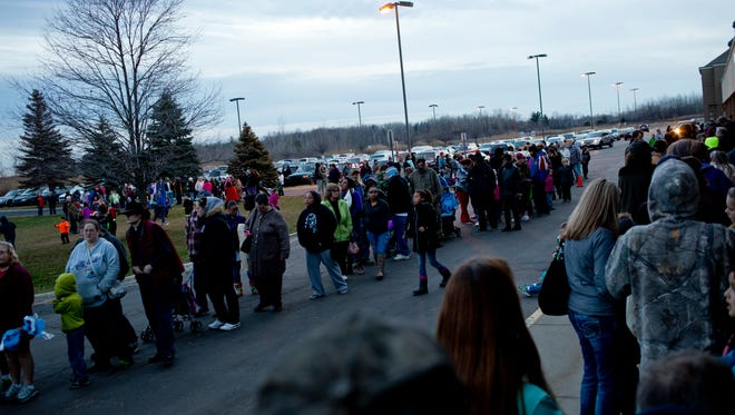 Hundreds of people line up outside during the Grace Ministry Center and Community Action Agency's Reverse Christmas Friday, Dec. 11, 2015 at the Factory Shops outlet in Kimball Township.