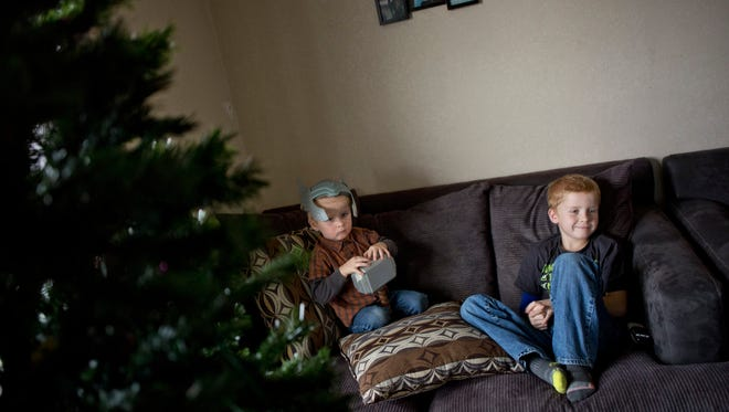 Landon Agosta, 8, rests on the couch with his brother Preston, 2, while they watch cartoons Thursday, Dec. 10, 2015 at his home in Marine City. Landon is undergoing treatment for skin cancer.