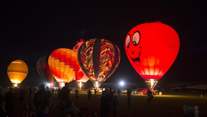 Balloons sit grounded during the Desert Glow event where pilots each take turns lighting up their envelopes with their propane burners during the Arizona Balloon Classic at the Fear Farm Sports and Entertainment Complex on Jan. 23, 2015, in Phoenix.
