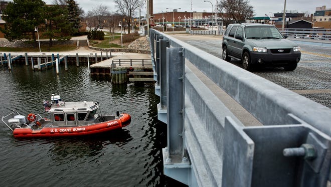 A Coast Guard boat travels along the Black River as traffic passes over the Seventh Street Bridge  Tuesday, Dec. 15, 2015  in Port Huron. The bridge is owned and operated by the City of Port Huron.