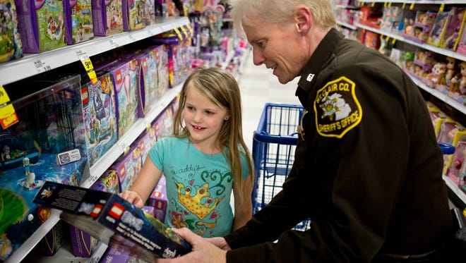 St. Clair County Sheriff's Deputy Patti Muxlow looks at a toy with Adriannah Pelka, 7, of Marine City, during Shop with a Cop Tuesday, Dec. 15, 2015 at Meijer in Fort Gratiot.