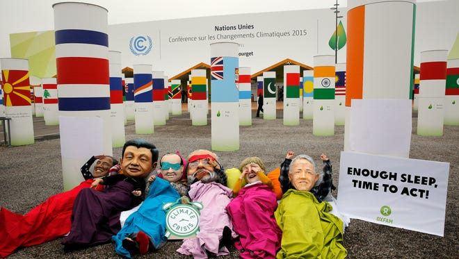Oxfam activists wear masks of world leaders as they stage a protest during the COP21, United Nations Climate Change Conference in Le Bourget, north of Paris, Thursday, Dec. 10, 2015.