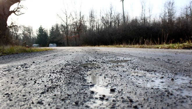 Potholes are seen in the roadway Dec. 23 along 36th Street in Port Huron Township. Warm winter weather has decreased the need for salt on paved roads, but is deteriorating gravel and limestone roads more quickly.