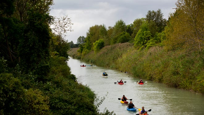 Kayakers paddle along the Black River canal during Paddle and Pour Saturday, September 12, 2015 in Port Huron.