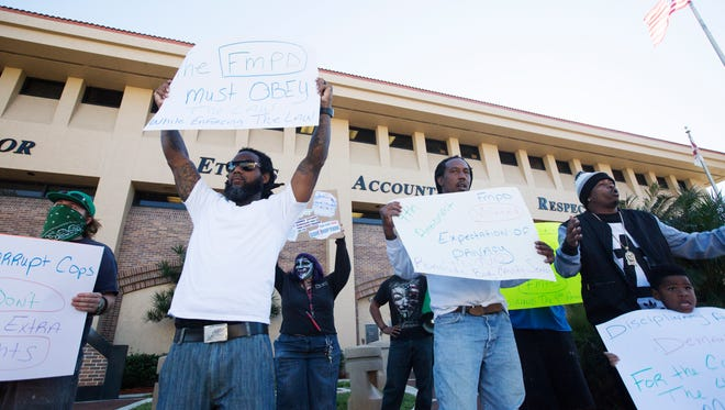 Todd Chrisp, second from left, led a group of small protesters at the Fort Myers Police Department who protested alleged police mistreatment and illegal searches.