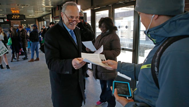 U.S. Senator Chuck Schumer give out flyers to commuters at the Metro-North White Plains train station announcing an increase in tax breaks for using mass transit on Jan. 11, 2016.